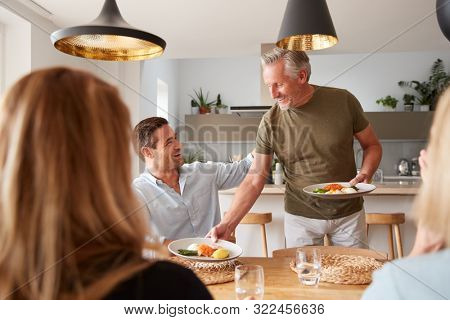 Family With Senior Parents And Adult Offspring Eating Brunch Around Table At Home Together