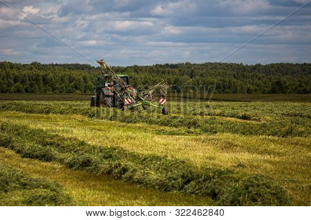 Tula, Russia - July 30, 2019: Green Haymaking Tractor On Summer Field Before Storm - Telephoto Shot