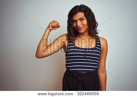 Transsexual transgender woman wearing striped t-shirt over isolated white background Strong person showing arm muscle, confident and proud of power