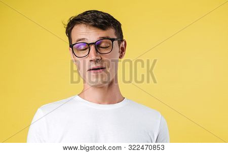 Portrait Of A Young Man With Glasses With His Eye Closed. Sleepy Man With Closed Eyes