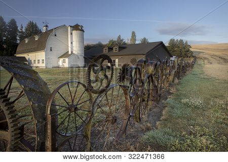 Gears And Wheel As A Fence In Eastern Washington. An Early Morning Photo Of The Artisan Barn In The