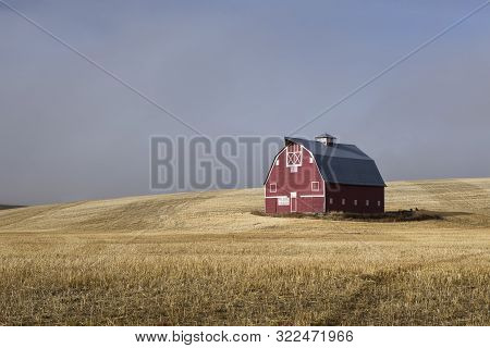 Clearing Fog And Morning Sun Show Off A Red Barn. A Red Barn Stands In A Harvested Field With The Li