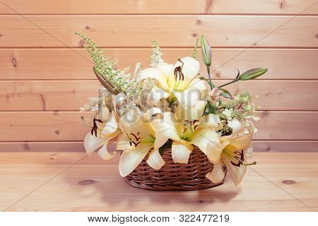 Wicker Basket With Beige Colored Lilies And White Astilbe And Hydrangea Flowers On Wooden Table. Vie
