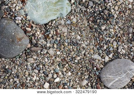 Stones Texture. Background The Damp Multi-colored Pebbles Close Up Soft Focus From On The Pebbly Bea