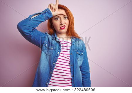 Beautiful redhead woman wearing denim shirt and striped t-shirt over isolated pink background making fun of people with fingers on forehead doing loser gesture mocking and insulting. poster