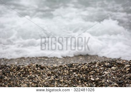 A Sea Foam Is White The During A Surf. It Is The Rest On The Rocky Beach.