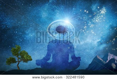 Silhouette Of Man Practicing Meditation Outdoors In Night Under Starry Sky