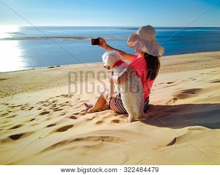 Beautiful Woman Travelling With Dog, Using Smart Phone With Sea View Background. Sitting On Sandy Be