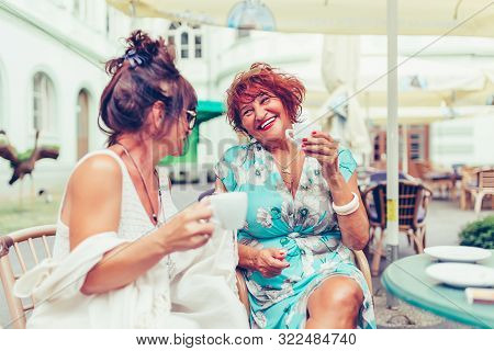 Two Smiling Senior Women Talking And Drinking Coffee  In A Outdoor Cafe