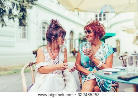 Two Happy Senior Women Talking And Drinking Coffee In A Outdoor Cafe