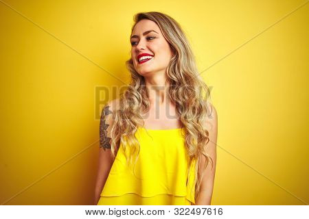 Young attactive woman wearing t-shirt standing over yellow isolated background looking away to side with smile on face, natural expression. Laughing confident.