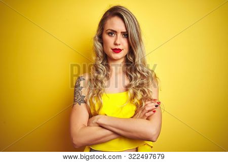 Young attactive woman wearing t-shirt standing over yellow isolated background skeptic and nervous, disapproving expression on face with crossed arms. Negative person.