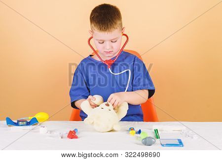 Health Care. Kid Little Doctor Busy Sit Table With Medical Tools. Medical Examination. Medicine Conc