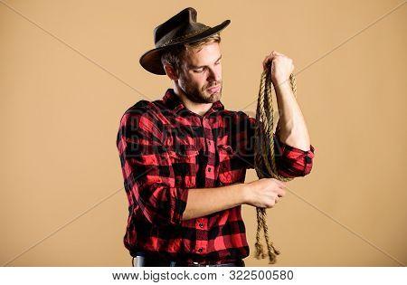 Lasso Tool Of American Cowboy. Western Life. Man Cowboy Beige Background. Man Wearing Hat Hold Rope.