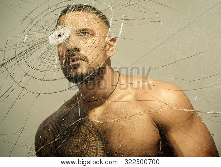 Power and vitality. Latino man full of power and energy looking through broken glass. Strong hispanic guy training power and endurance. Developing of muscular power and strength. poster