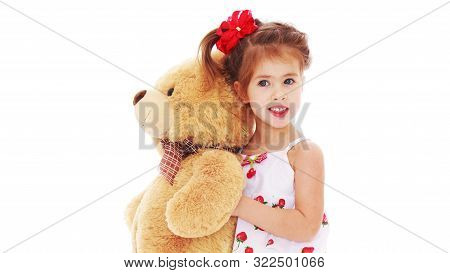 Little Girl With A Teddy Bear. The Concept Of The Game, Raising A Child In Kindergarten And In The F