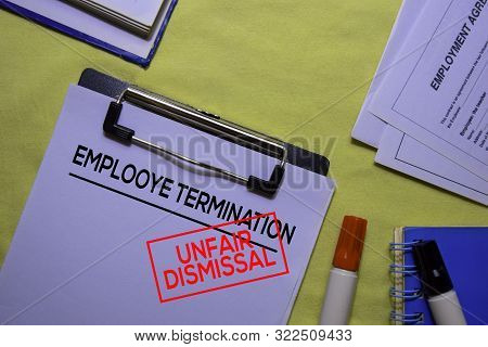 Employee Termination Text On Document Form And Stamp Unfair Dismissal Isolated On Office Desk.