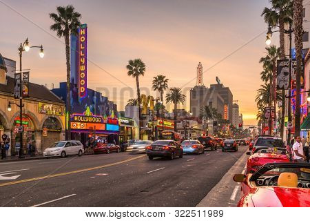 LOS ANGELES, CALIFORNIA - MARCH 1, 2016: Traffic on Hollywood Boulevard at dusk. The theater district is famous tourist attraction.