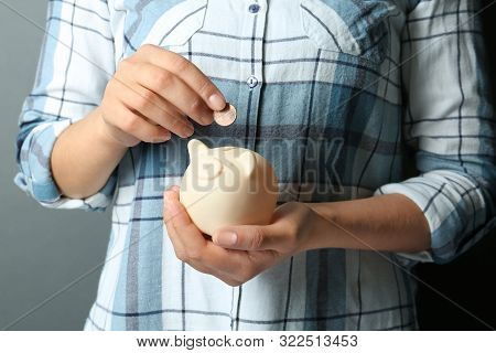 Young Woman Putting Coin Into Piggybank On Grey Background, Closeup View