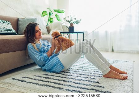 Playing With Cat At Home. Young Woman Sitting On Carpet And Hugging Pet.