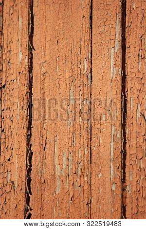 Background Of Ocher Peeling Oil Paint Upon An Old Wooden Wall