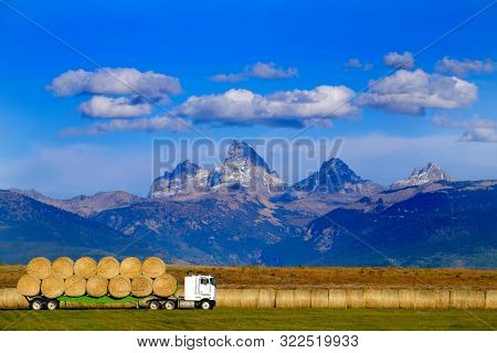 Truck hauling load of freshly harvested hay with Teton Mountains in Background