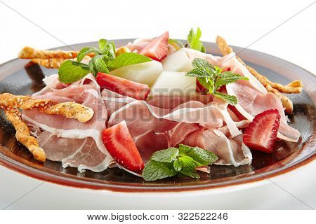 Thinly sliced Italian prosciutto, prosciutto crudo or crudo with melon, strawberry and crostini close up isolated on white background. Macro Photo of dry-cured uncooked ham with green mint leaves