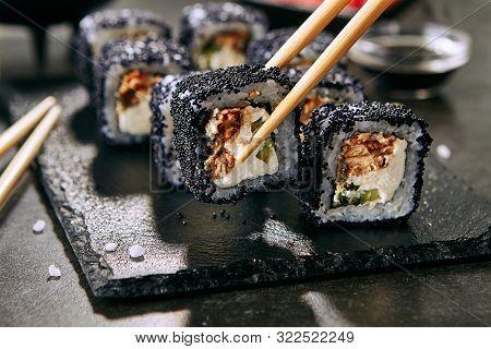 Chopstick holding unagi maki rolls with rice, cream cheese, eel, cucumber, flying fish black caviar and nori closeup. Fresh japanese uramaki rolls with tobiko on black slate plate background