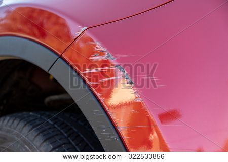 Closeup Of Deep Scratches In Red Paint Of Car Bumper
