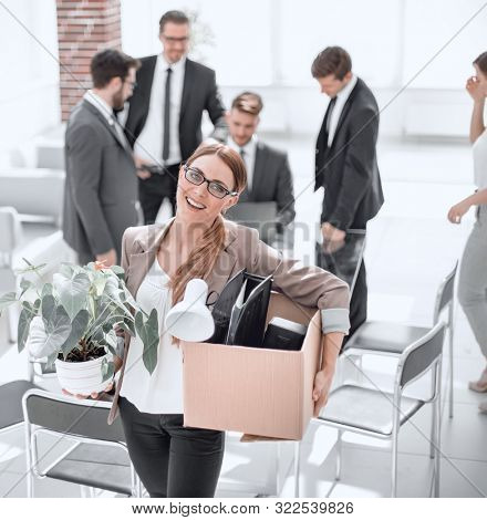 smiling business woman with personal things standing in modern office