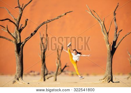 Adorable girl among dead camelthorn trees surrounded by red dunes in Deadvlei in Namibia