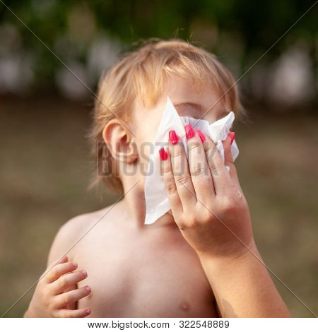 Hygiene - mom wiping the baby nose and face with wet wipes. Cleaning wipe, pure, clean, outdoor