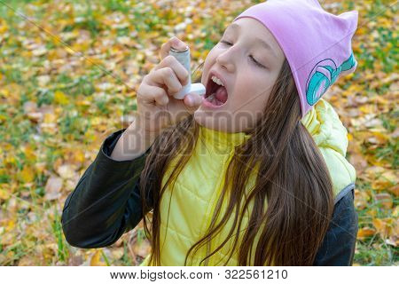 A Girl In A Hat And Jacket Takes Medicine In The Form Of An Inhaler For Bronchial Asthma In The Autu