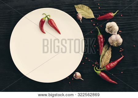 White Plate Garlic Red Chili Pepper On Black Wooden Background
