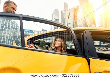 Photo Of Man Giving Hand To Woman Sitting In Back Seat Of Taxi On Summer Day Against Backdrop Of Mod