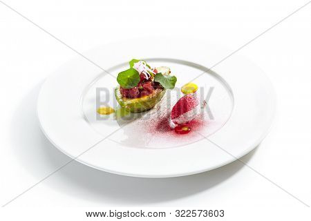 Tuna tartar made from raw fish served in avocado with lime ice cream on white restaurant plate isolated. Exquisite serving yellowfin sashimi tatar in alligator pear with gourmet dessert closeup poster