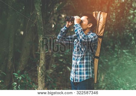 Man With Binoculars Telescope In Forest Looking Destination As Lost People Or Foreseeable Future. Pe