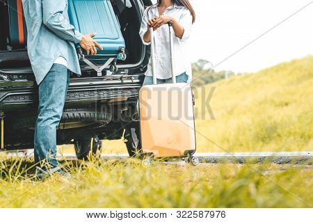 Closeup Lower Body Of Couple Lift Down Trolly Luggage At Back Of Suv Car Trunk Along Road Trip With
