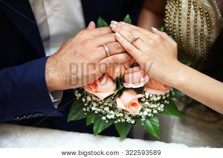 A Newly Engagement Couple Place Their Hands On A Wedding Bouquet Showing Off Their Wedding Rings. A