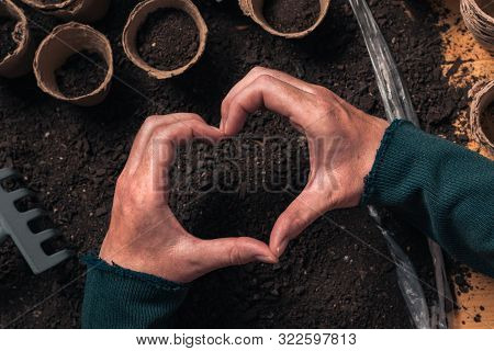 Gardener Hand Heart Gesture Over The Table With Organic Gardening And Farming Equipment, Close Up Of