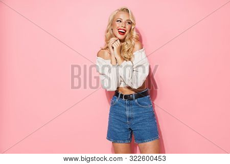Image of charming blonde woman with long curly hair wearing trendy clothes smiling and posing at camera isolated over pink background