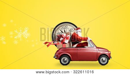 Christmas countdown arriving. Santa Claus on snowy toy car delivering New Year gifts and clock at yellow background