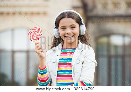 Happy kid singing sweet candy mic. Happy childhood. Kid child headphones holding lollipop candy. Happy kid with candy outdoors having fun. Calories and energy. Schoolgirl deserve dessert. Sweet remix. poster