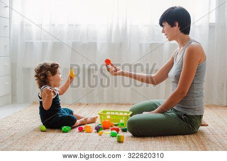Mother And Child Play On The Floor In The Nursery. Mom And Little Baby Boy Are Doing With Plastic Co
