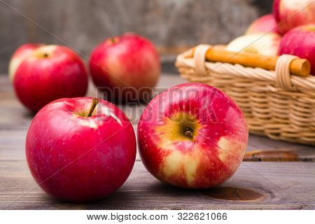 Ripe Red Apples And Basket With Apples On A Wooden Table. Close-up