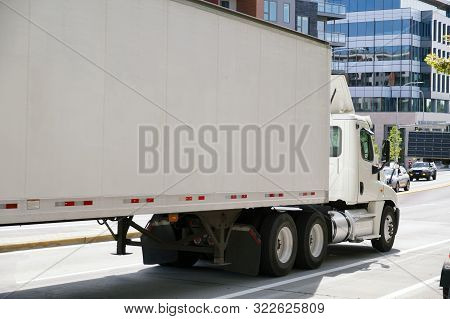 A City On The East Coast Of The Usa. A Large Truck With A Semitrailer In City Traffic.