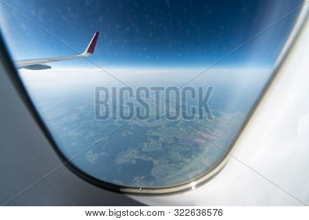 Airplane Window View To Cloudy Sky And Earth. Beautiful Landscape From Aircraft Cabin. Flying Withou