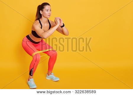 Close Up Of Athletic Woman In Squat In Gym, Fit Girl Exercising With Resistance Band For Lower Body