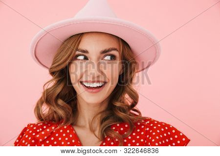 Image of a cheerful young pleased positive woman posing isolated over pink wall background wearing hat looking aside to copyspace.