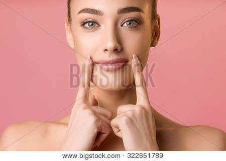 Natural Beauty. Young Woman Applying Lip Balm, Holding Fingers Near Lips, Pink Background